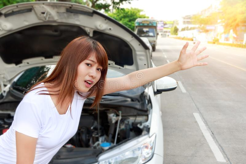 Woman looking for help after a car breakdown, standing besides c royalty free stock images