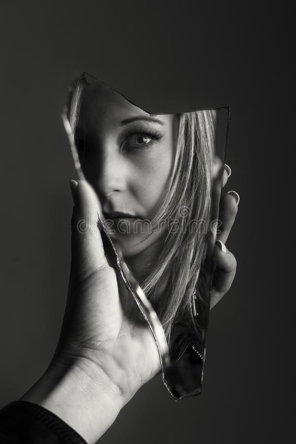 Woman looking at her face in a shard of broken mirror artistic c royalty free stock images