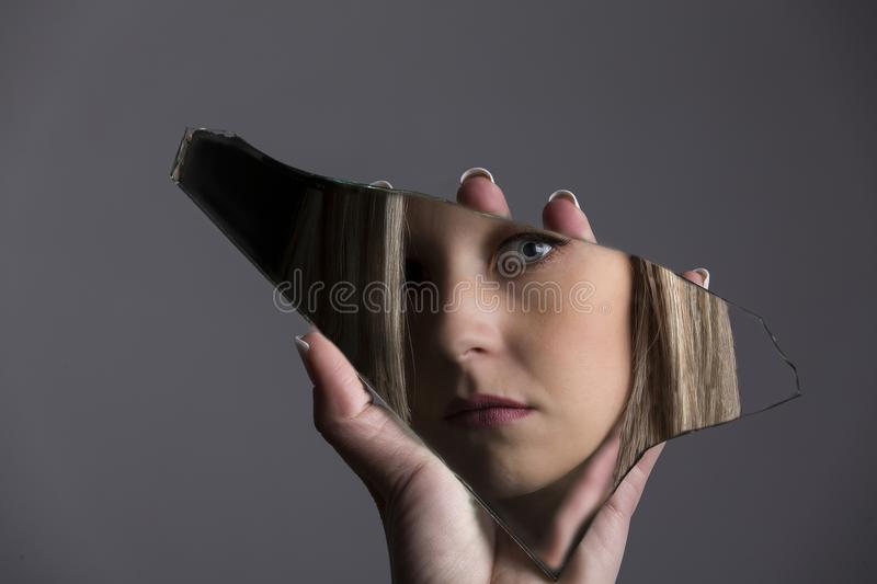 Woman looking at her face in shard of broken mirror stock photography