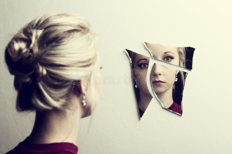 Woman looking at her face in three shards of broken mirror stock photography