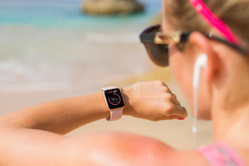 Woman looking at her heart rate data on smartwatch. Woman doing workout on the beach stock images