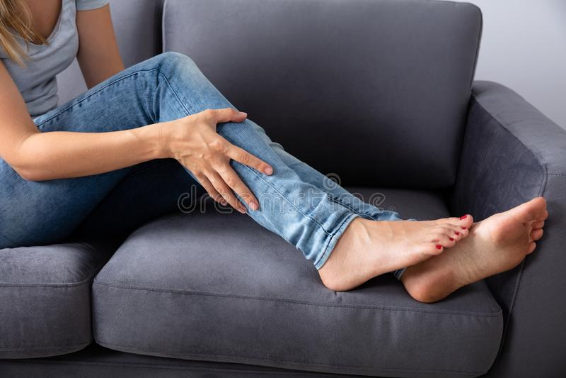 Woman Looking At Her Injured Leg royalty free stock image