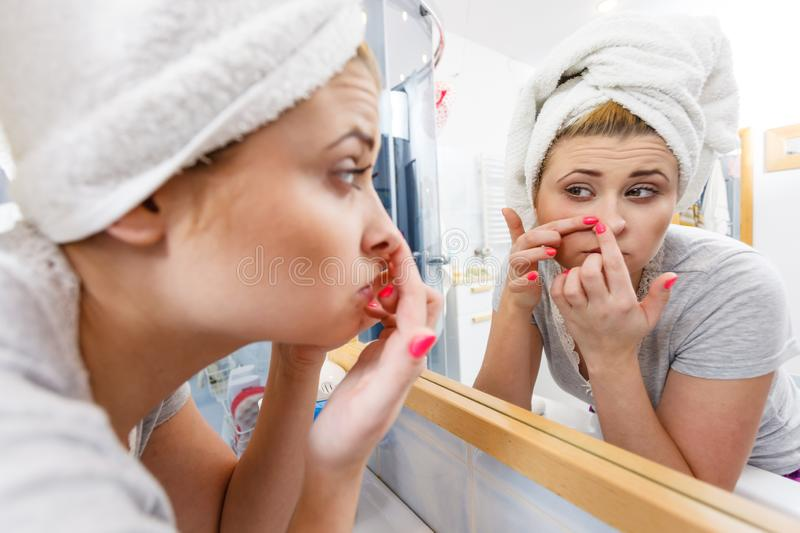 Woman looking in mirror dealing with acne royalty free stock image