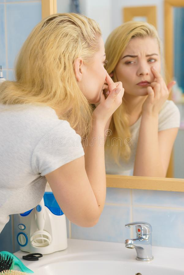 Woman looking at her skin in mirror stock images