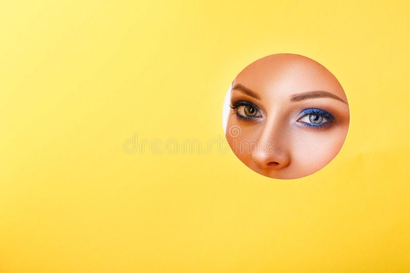 Woman looking in the hole, bright beautiful makeup, big eyes and lips, bright lipstick, professional cosmetics and facial care. stock photo