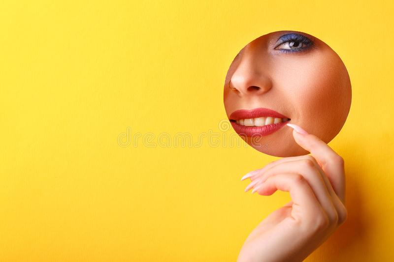 Woman looking in the hole, bright beautiful makeup, big eyes and lips, bright lipstick, professional cosmetics and facial care. royalty free stock images