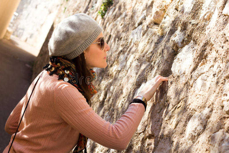 Woman Looking Into A Hole In A Stone Wall. Interested Woman Looking Into A Hole In A Stone Wall royalty free stock image