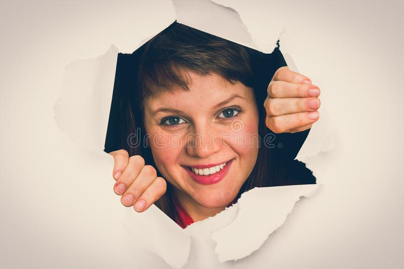 Woman is looking through a hole in torn paper royalty free stock image