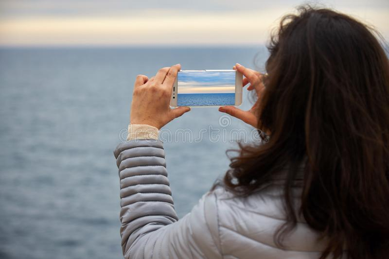 Woman looking at infinite sea and take picture with mobile phone.  royalty free stock photo
