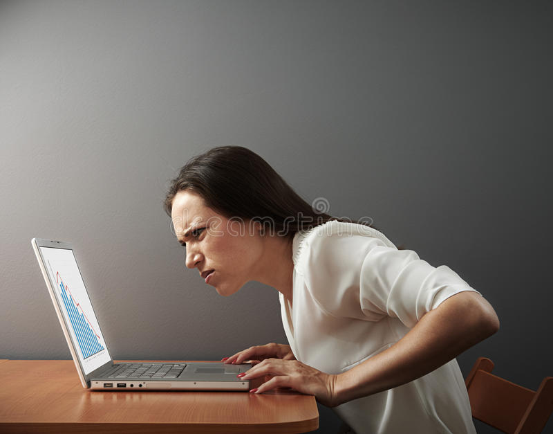 Woman looking at laptop with distrust. Young woman looking at laptop with distrust stock photo