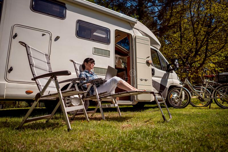 Family vacation travel, holiday trip in motorhome RV. Woman looking at the laptop near the camping . Caravan car Vacation. Family vacation travel, holiday trip stock photo