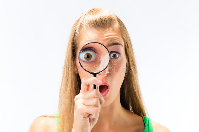 Woman looking through magnifying glass stock photography