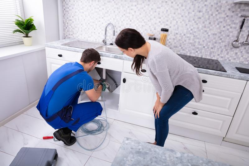 Male Plumber Cleaning Clogged Sink Pipe With Drained Cable. Woman Looking At Male Plumber Cleaning Clogged Sink Pipe With Drained Cable In Kitchen stock image