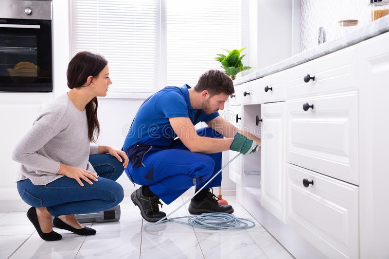 Male Plumber Cleaning Clogged Sink Pipe With Drained Cable. Woman Looking At Male Plumber Cleaning Clogged Sink Pipe With Drained Cable In Kitchen stock photos