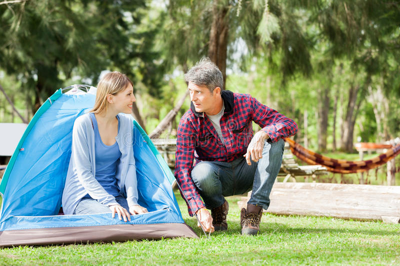 Woman Looking At Man Preparing Tent In Park royalty free stock images