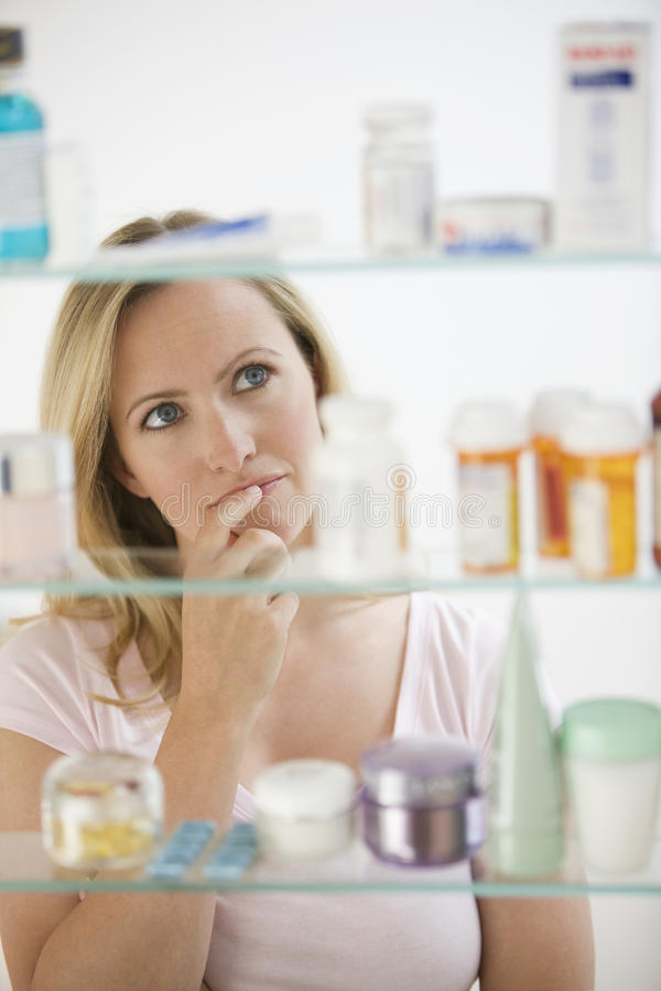 Woman Looking in Medicine Cabinet. A young woman is looking through her medicine cabinet. Vertical shot royalty free stock image