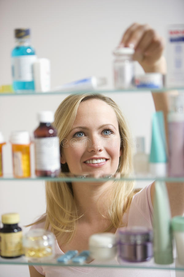 Woman Looking in Medicine Cabinet. A young woman reaches for a container in her medicine cabinet. Vertical shot stock photography