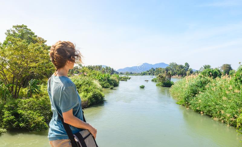Woman looking at the Mekong River on the 4000 islands Laos daytime, famous travel destination backpacker in South East Asia stock image