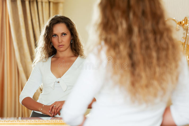 Beautiful fashion woman looking in the bedroom mirror royalty free stock photo