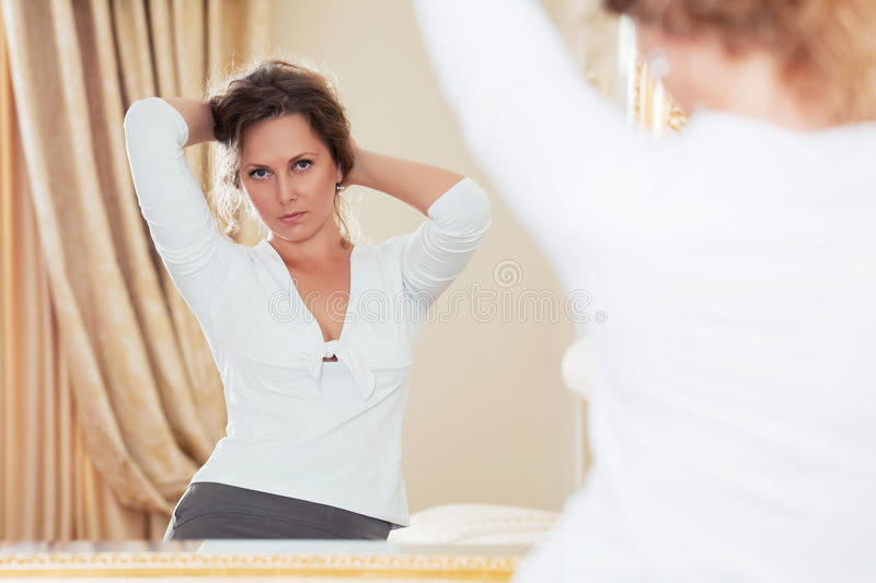 Fashion woman looking in the mirror at apartment royalty free stock image