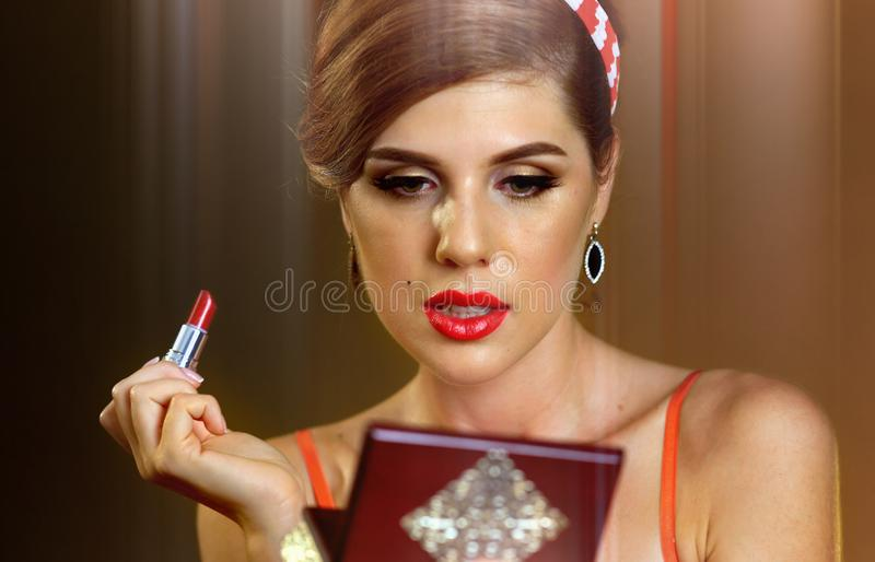 Woman looking mirror and apply shiny red lipstick stock photo