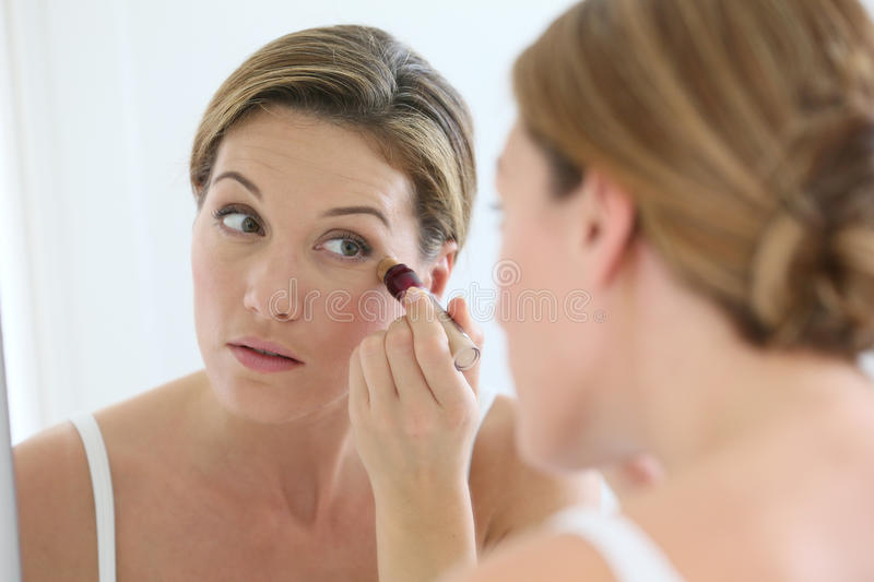 Woman looking at the mirror applying a concealer royalty free stock photos