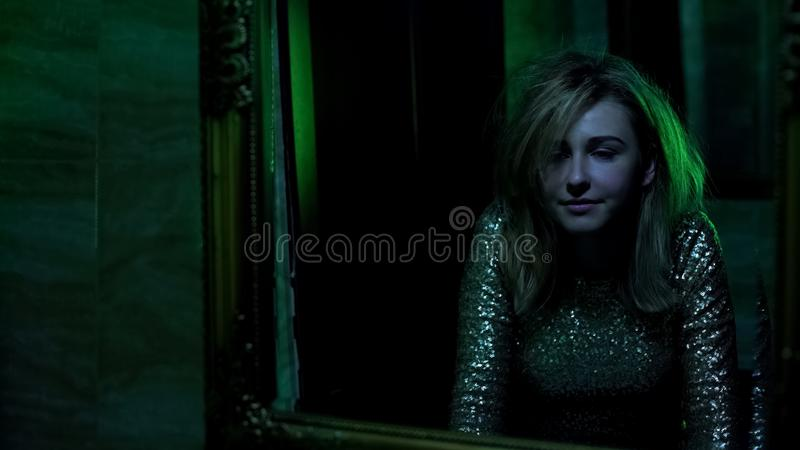 Woman looking in mirror, euphoria after snorting cocaine in night club toilet. Stock photo stock photo