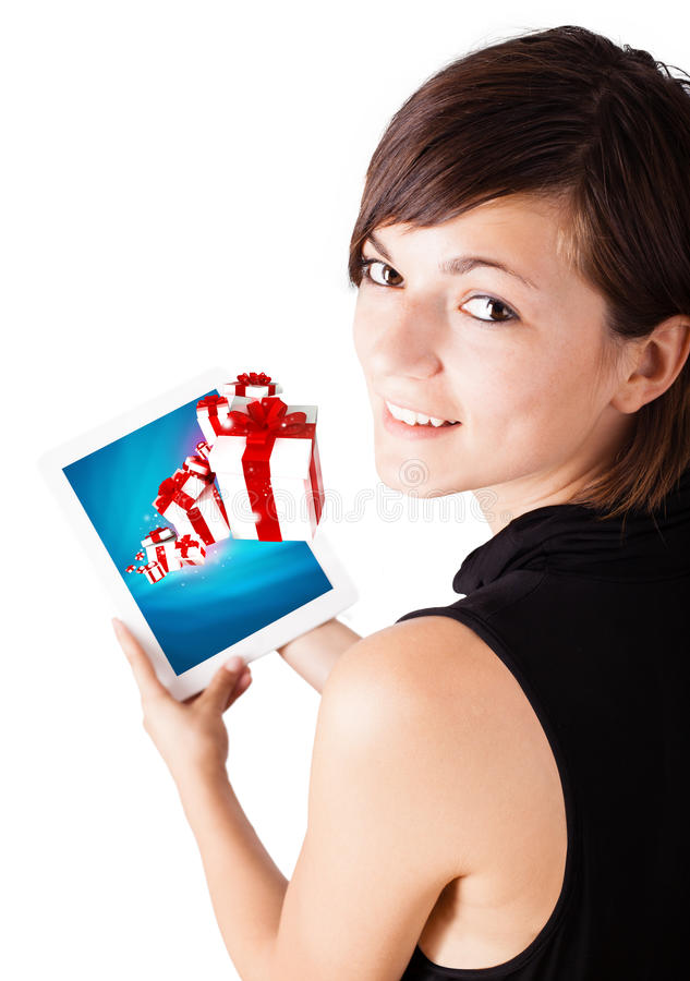 Woman looking at modern tablet with present boxes