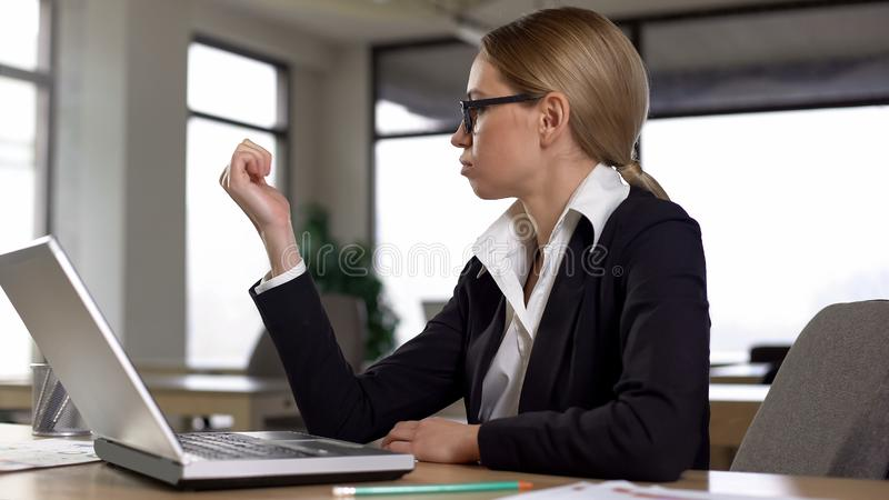Woman looking at nails from boredom at work in office, lack of motivation. Stock photo stock image