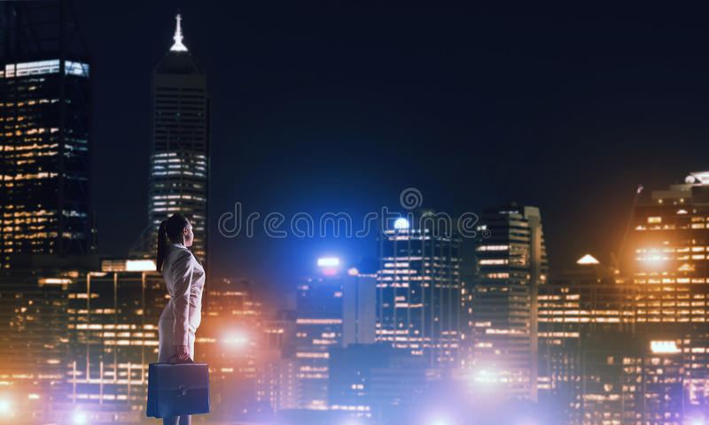 Woman looking at night city. Rear view of elegant businesswoman viewing lights of night city royalty free stock images
