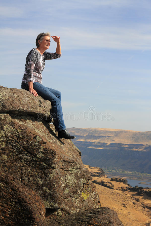 Woman Looking. An older woman sitting on a high rock point viewing looking out at the river territory under blue skies. Copy space royalty free stock photos