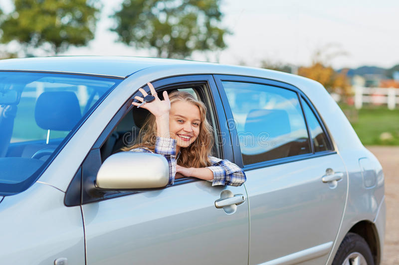 Woman looking out of the car window and holding a key. Beautiful young driver looking out of the car window holding a key stock photography