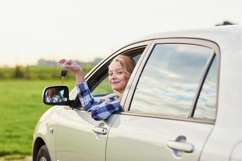 Woman looking out of the car window and holding a key. Beautiful young driver looking out of the car window holding a key stock photo