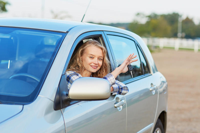 Woman looking out of the car window and holding a key. Beautiful young driver looking out of the car window holding a key royalty free stock photos