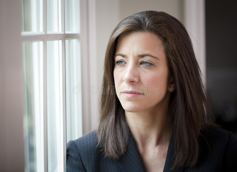Woman looking out of window stock image