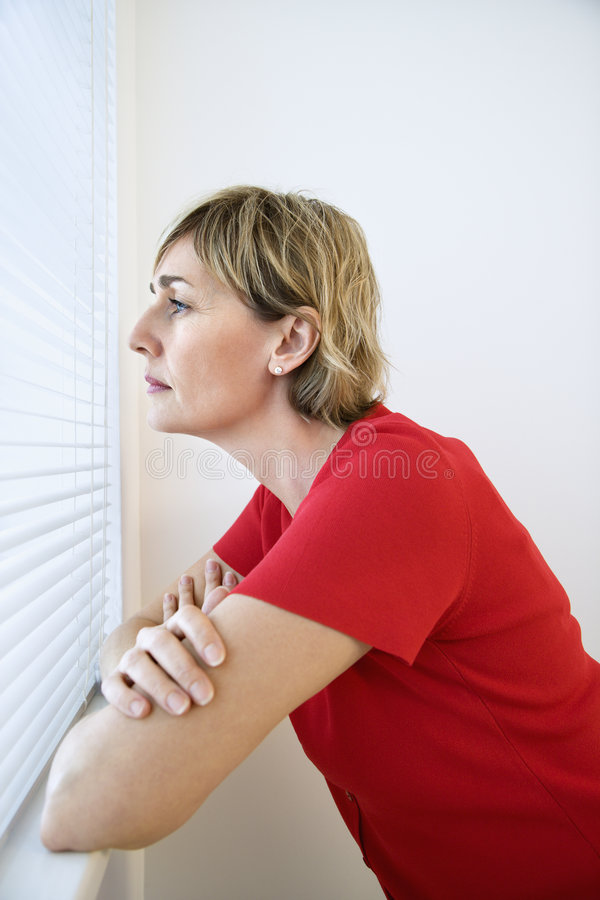 Woman looking out window. stock photo