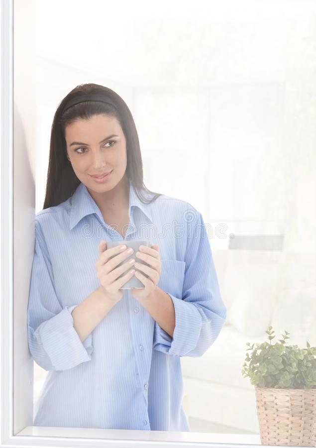 Woman looking out of window with coffee royalty free stock photos