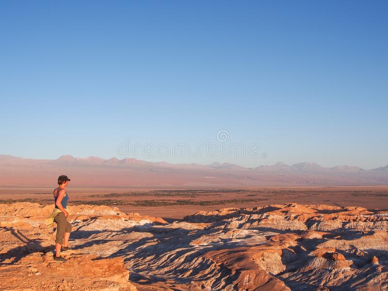 Woman looking over Mars Valley or Death Valley, Atacama desert, during sunset royalty free stock photography