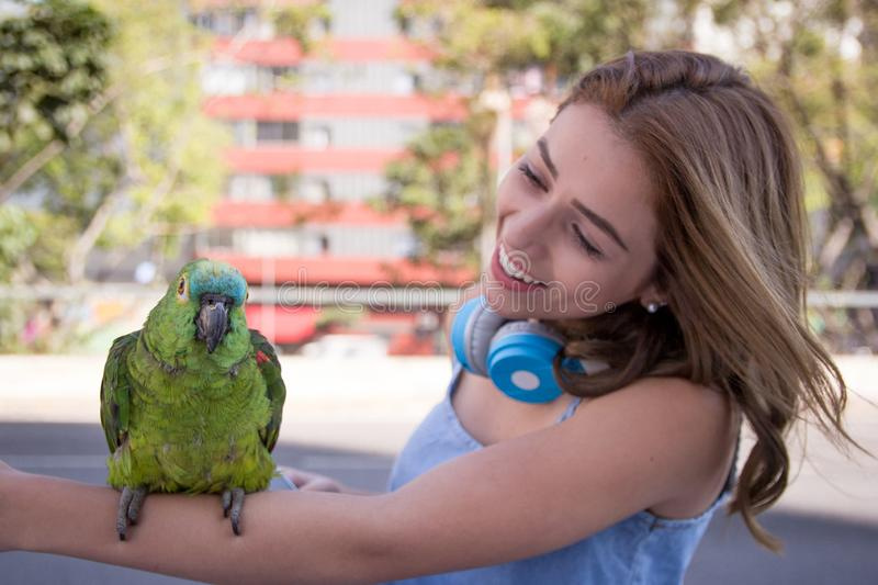Woman looking at parrot in her arm in urban background with buildings. Blonde young woman looking at parrot in her arm in urban background with buildings during stock photo