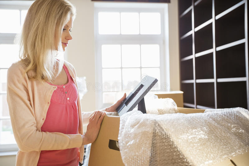 Woman looking at photo frame while unpacking moving boxes at new house royalty free stock photos