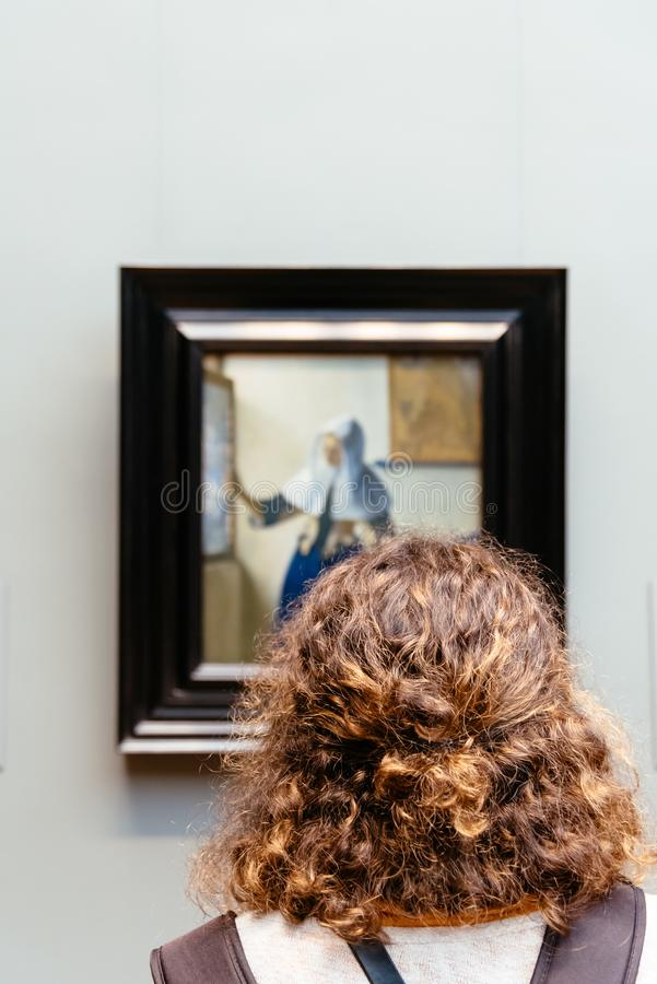 Woman looking at picture at Metropolitan Museum of Art. New York City, USA - June 23, 2018: Woman looking at picture at Metropolitan Museum of Art. The MET is royalty free stock image