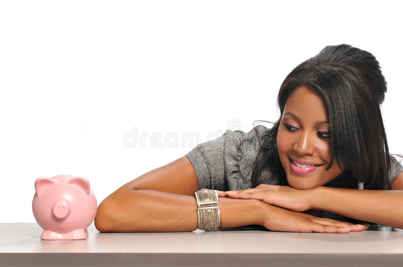Woman looking at a piggy bank royalty free stock images