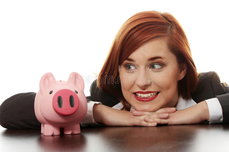 Woman looking on pink piggy bank stock photo