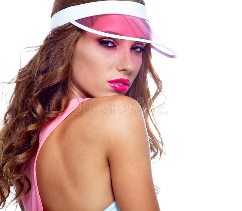 Woman looking through the pink sun visor at camera. In studio royalty free stock photography