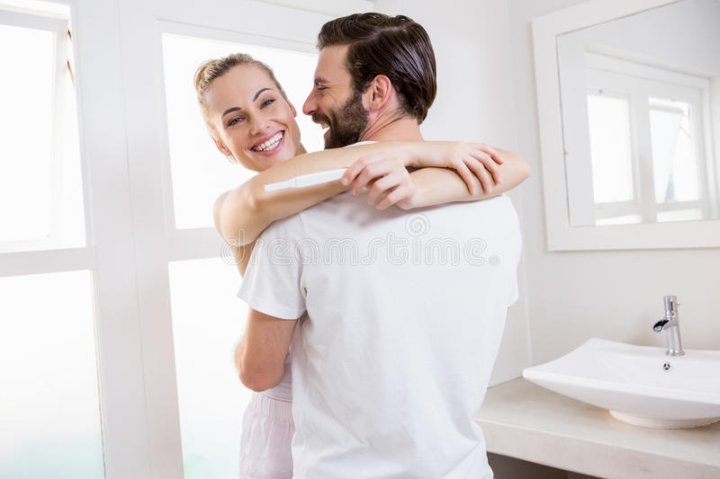 Woman looking at pregnancy test while embracing a man stock photography