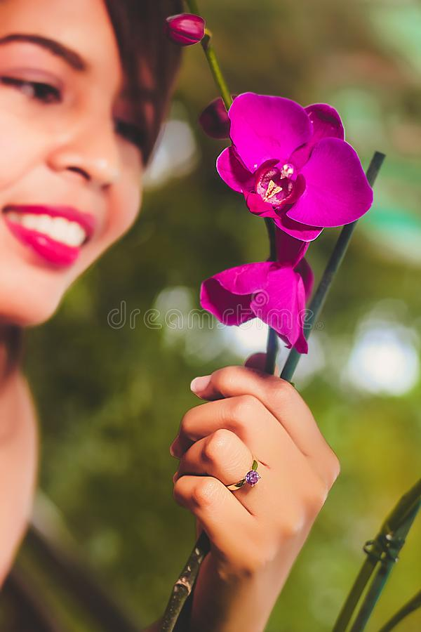 Woman looking at purple orchids stock photography