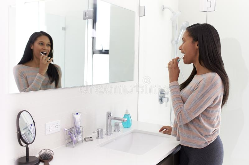 Woman Looking At Reflection In Bathroom Mirror Brushing Teeth stock photography
