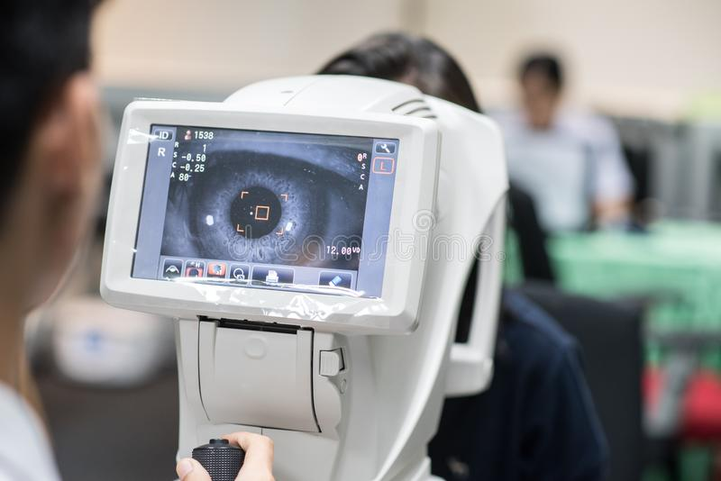 Woman looking at refractometer eye test machine in ophthalmology. For your artwork royalty free stock photos