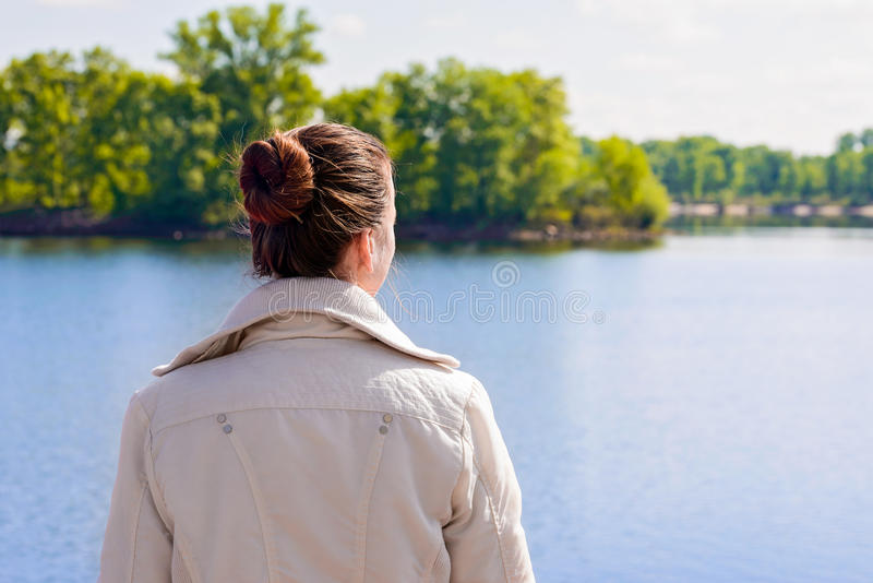 Woman Looking at the River. A woman with a chignon looking at the river during a nice sunny spring morning royalty free stock images