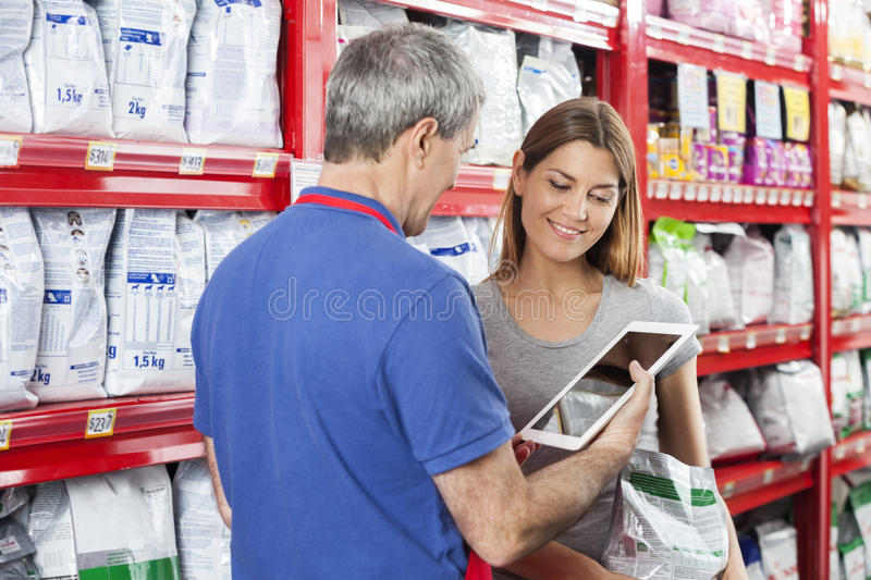 Woman Looking At Salesman Using Digital Tablet In Pet Store. Woman holding pet food while looking at salesman using digital tablet in store royalty free stock photos